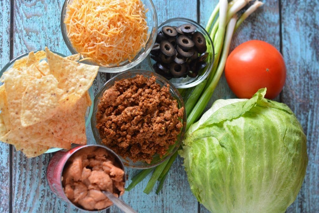 Ingredients for Taco Bake, with cheese, black olives, lettuce, beans, and tomatoe