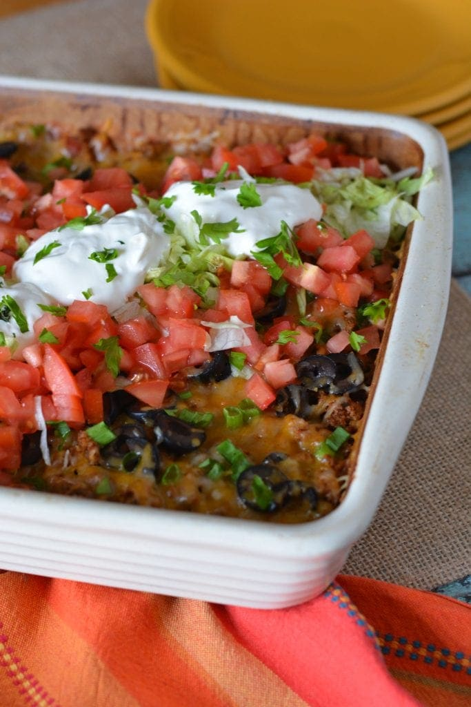 taco bake in a white dish topped with tomatoes, sour cream, black olives, beans and onion
