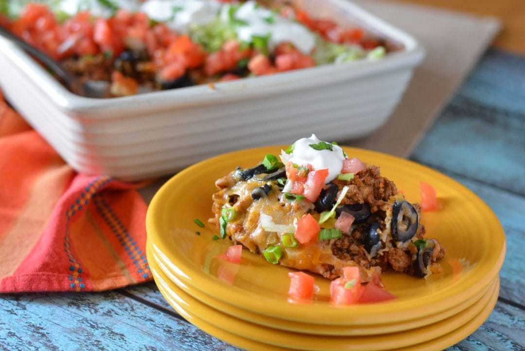 taco bake served on yellow dish, topped with black olives, sour cream, and tomatoes