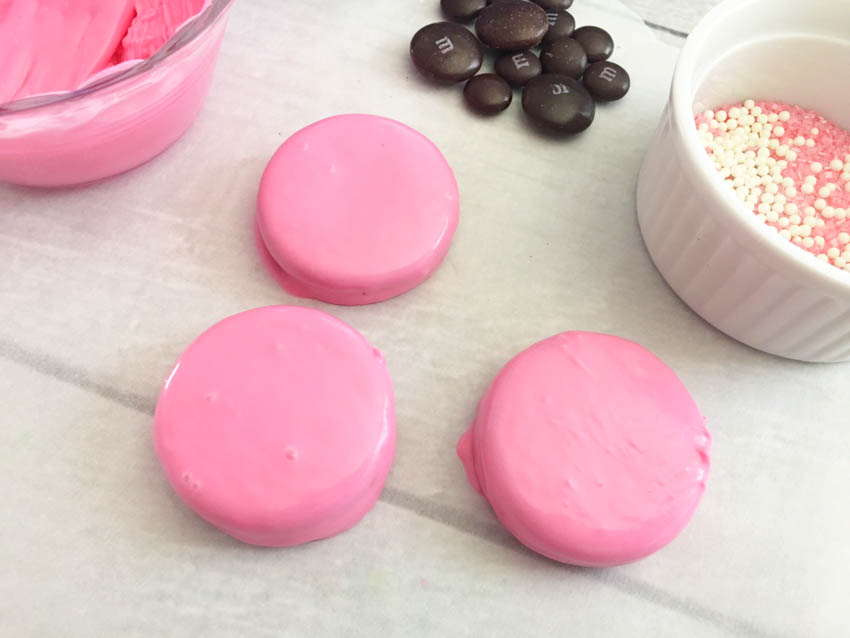 Dunk an Oreo into your melted pink chocolate, let an excess drop off, and place onto your parchment paper.