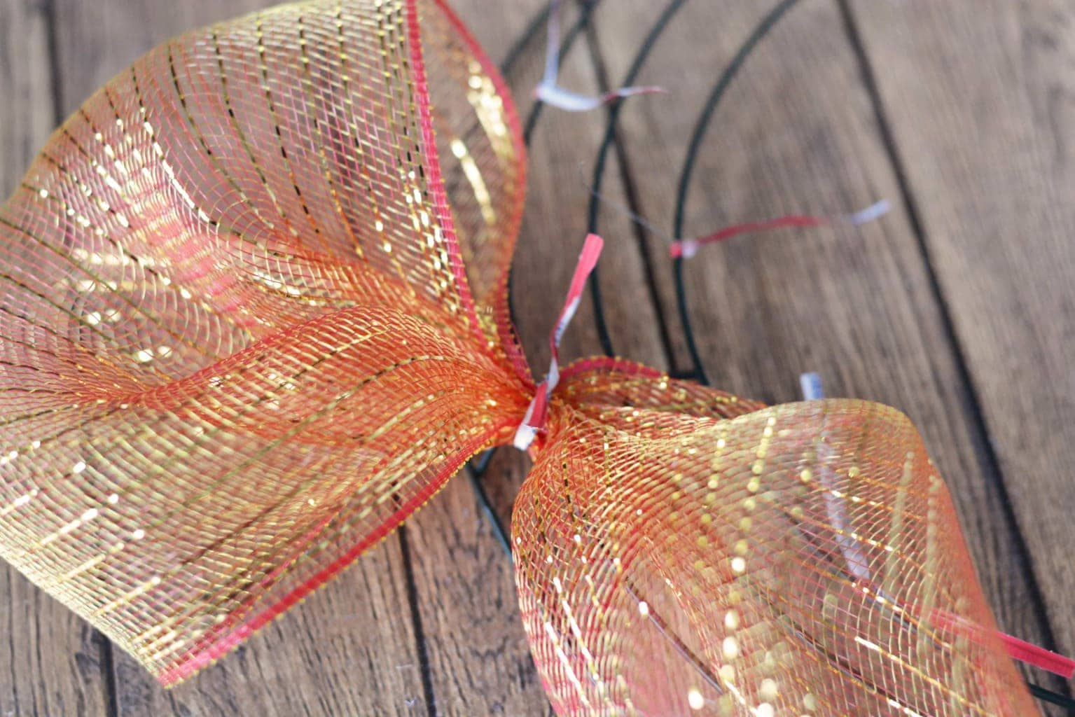 """Continue by using about 8"""" of mesh and scrunching it and attaching it to the twist ties on the wire frame. Continue all the way around the wreath frame. I used the entire roll of mesh for one wreath."""