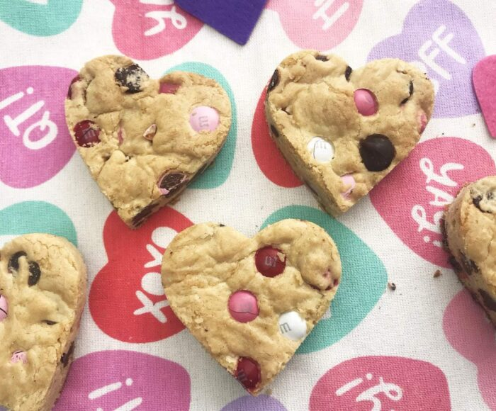 These Chocolate Chip Heart Shaped Cookie Bars are the one Valentine Day treat that you just can't miss! Made with Valentine's M&M's. They are simple to make and full of love! #HeartShapedCookies #CookieBars #ValentinesDayRecipes